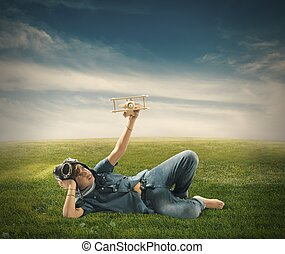 Young boy playing with toy airplane in a green field