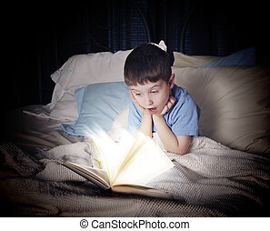 Child Reading Open Book at Night in Bed - A little boy is...