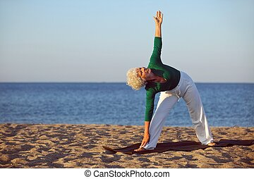 Senior woman performing stretches on the beach