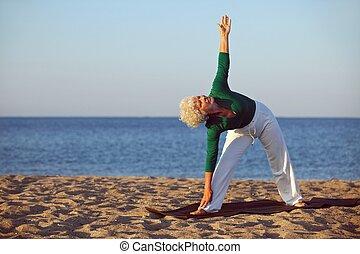 Senior woman performing stretches on the beach - Senior...