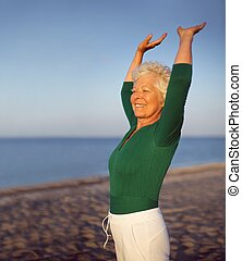 Old caucasian woman exercising outdoors to stay fit -...