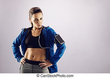 Fit young woman posing confidently in sportswear