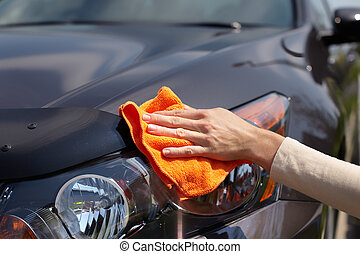 Hand polishing car - Hand with microfiber cloth cleaning car...