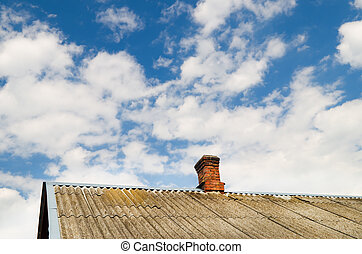 Roof of the house with a brick pipe against the cloudy sky