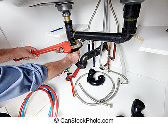 Hands of Plumber with a wrench. - Hands of professional...