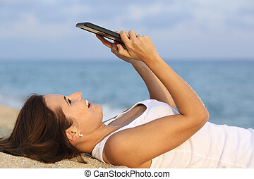 Side view of a teenager girl browsing her tablet pc lying on...