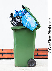Rubbish sacks in bin - Blue and black rubbish sucks in a...