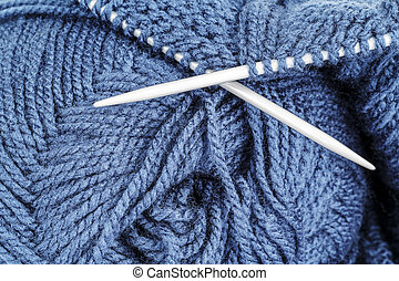 Woolen thread and knitting needle shown closeup