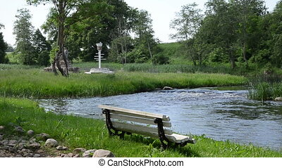 solitary white bench - fast flowing stream near is located...