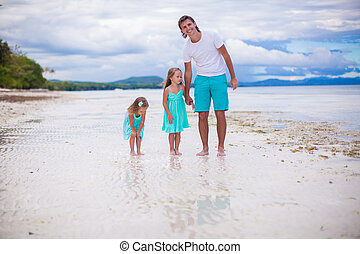 Little girls walking around with dad on a tropical beach