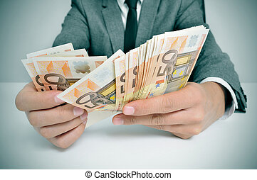 man in suit with counting euro bills - a man wearing a suit...