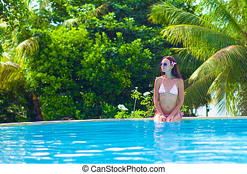 Beautiful young woman enjoying the luxury quiet swimmingpool