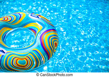 Inflatable colorful Rubber Ring floating in blue swimming...