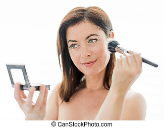 Woman in her forties applying makeup - portrait of a...