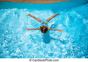 Little cute happy girl swims in the swimming pool