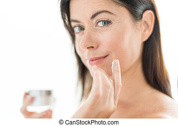 Woman in her forties applying face cream - portrait of a...