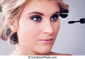 Closeup of Girl applying Eye Makeup. - Woman looking in a...