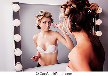 Woman at Makeup Miiror. - Girl applying face makeup at a...
