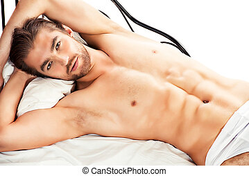 valentine - Handsome nude man lying in a bed Isolated over...