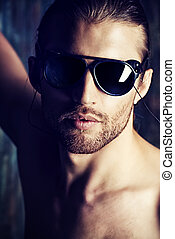sunglasses - Sexual muscular nude man posing over dark...