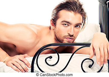 nude man - Handsome nude man lying in a bed. Isolated over...