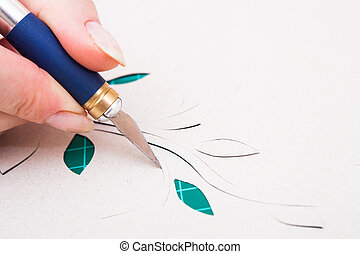 womans hand cutting flower from paper with paper-knife