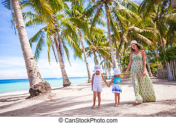 Mother walking with her two kids along a tropical beach