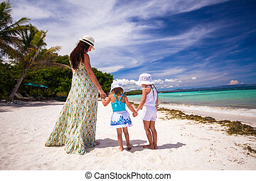 Rear view of two girls and their mother on a white, tropical...