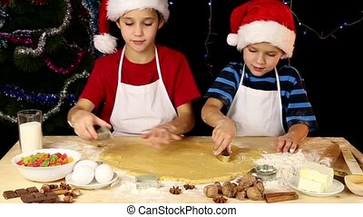 Two kids cutting the dough - Two kids cutting the Christmas...