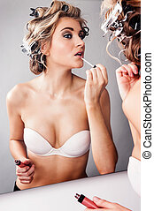 Girl Applying Makeup - Girl in hair curlers applying...