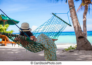 Adorable young woman lying in the hammock on tropical beach