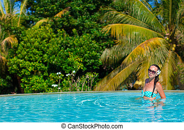 Young beautiful woman enjoying the luxury quiet swimmingpool