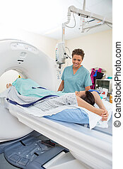 Nurse Looking At Patient About To Undergo CT Scan - Female...