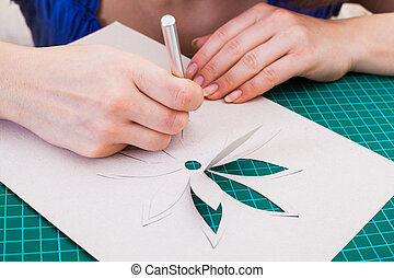 Womans hand cutting out flower from paper