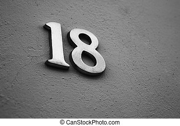 House Number 18 - white metallic number 18 hanging of a...