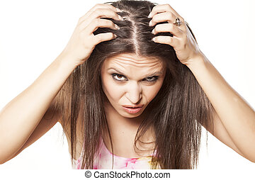 hair fall - nervous girl looking in the mirror her scalp