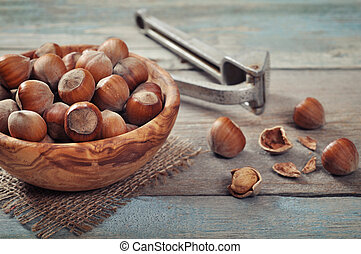Unpeeled hazelnuts in bowl on wooden background