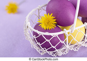 Colored eggs in a white basket on lilac background - Colored...
