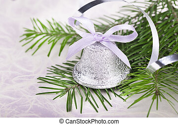 Christmas bell with fir-tree twigs on abstract background