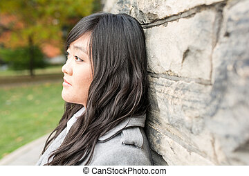 Woman standing against a brick wall