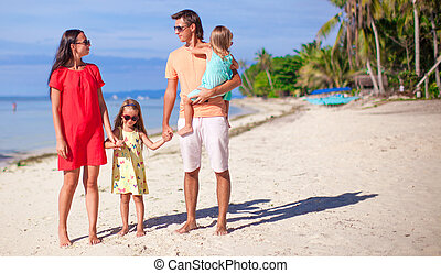 Beautiful family of four have fun on the beach in...