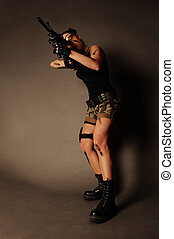 Woman with weapon. - Sexy army woman posing with weapon, on...