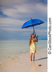 Little girl with an umbrella in hands on the sandy white beach