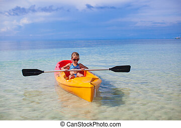 Little adorable girl kayaking in the clear blue ocean