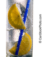 Glass of drink with ice cubes, straw and lemon slice