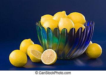 lemons in blue green bowl on blue background