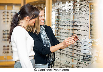 Happy Woman With Salesgirl Examining Eyeglasses - Happy...