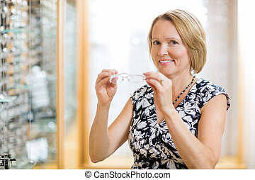 Woman Trying On Glasses At Optician Store - Portrait of...