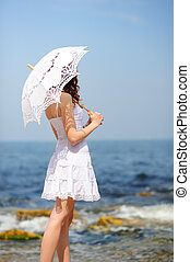 girl on a beach - girl in white dress with umbrella on a...