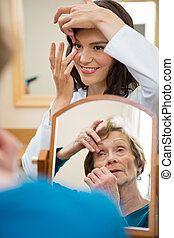 Optometrist Teaching Senior Woman To Insert Contact Lens -...